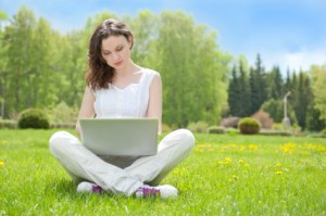 woman on laptop in grass
