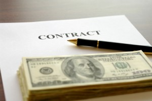 Contract page with pen and stack of dollars on table